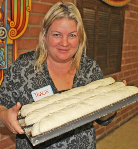 The loaves Tracie is holding have doubled in size from the rising process and are ready for the oven.