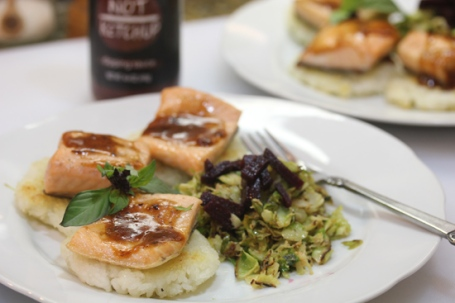 """Salmon on Crispy Rice Cakes topped with Smoky Date """"Not Ketchup"""" and """"Caesar"""" Brussels Sprouts."""